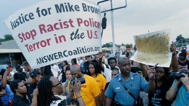 Missouri HIghway Patrol Capt. Ron Johnson walks among protesters on Aug, 16, 2014, as people protest the police shooting death of Michael Brown a week ago in Ferguson, Mo.