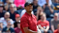 Tiger Woods reacts after playing his shot from the