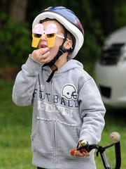 Jack Fiester, 6, of Newburgh nibbles on some cotton candy while sporting a new pair of glasses shaped like ice cream cones that he won while playing a ball toss game in the kid's park area set up in Sunrise Park in Evansville during a past Rockin River City Ride.