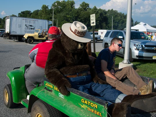 Smoky the bear gets a ride on a cart during National