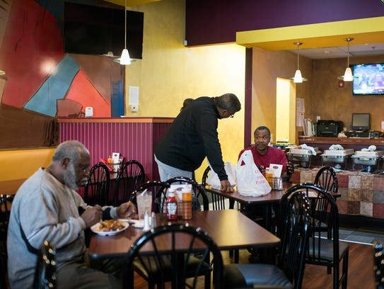 Operations manager Vernon Rochester, right, catches up with childhood friend Wesley Smith at Rochester's Barbecue and Grill Wednesday, in Lawnside. The Rochester family says they always cook like they're cooking for friends and family, especially since friends and family can appear anytime.