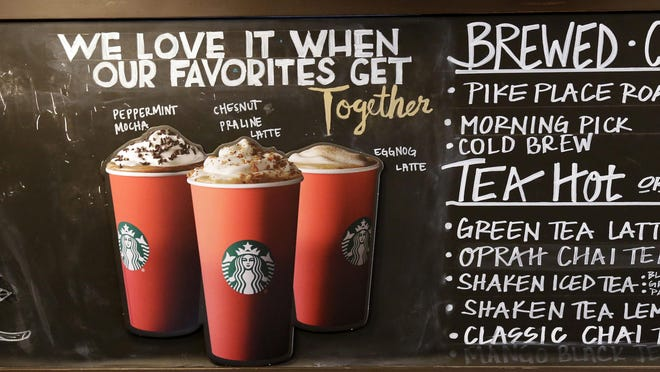 Red paper cups are featured on a chalkboard menu behind the counter at a Starbucks coffee shop in the Pike Place Market, in Seattle. Starbucks' minimalist new holiday coffee cup set off some complaints that the chain is waging war on Christmas.