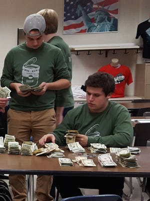Brighton High School's National Honor Society Treasurer Connor Cain, sitting, and member Sam Vaden each count a portion of the estimated $14,000 students and faculty raised in November for Gleaners Community Food Bank of Southeast Michigan.