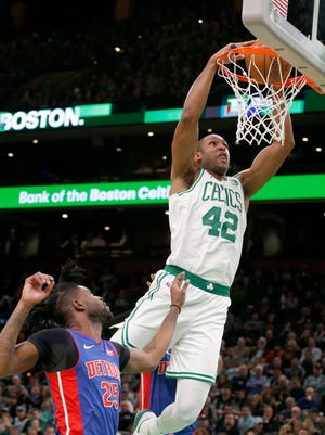 Boston Celtics center Al Horford (42) dunks the ball ahead of Detroit Pistons guard Reggie Bullock (25) during the first half of an NBA basketball game, Tuesday, Oct. 30, 2018, in Boston. (AP Photo/Mary Schwalm)