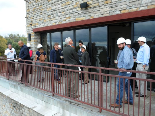Guest and members of the media look out over the Ohio River from a balcony area at Doc's Cantina during a guided tour.