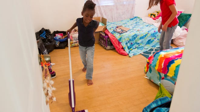 Cassyline, 5, mops the floor of her new room shared with her sister, Alyssa, 10, right, at their new house in Fort Myers.