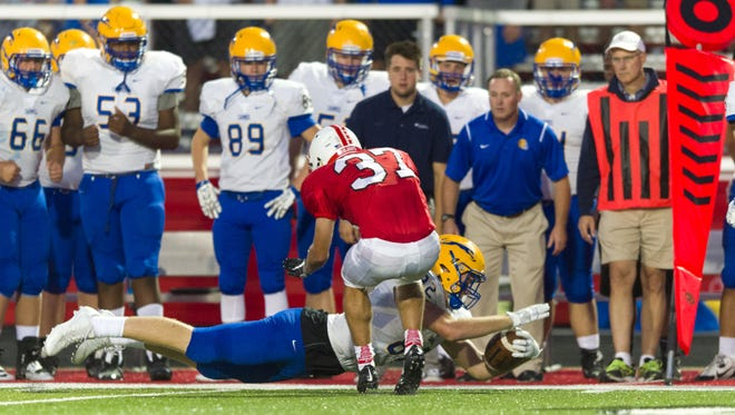 Carmel High School senior Kurt Rafdal (82) makes a diving effort to make the first down as he's contacted by Center Grove High School senior Logan Bontrager (37) during the second half of an IHSAA varsity football game, Friday, Sept. 2, 2016, at Center Grove High School. Center Grove won, 19-6.
