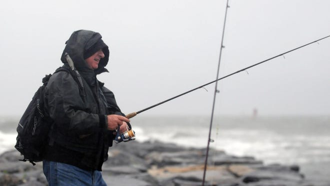 Fisherman Ian Burke stands on the rocks at the Indian River inlet fishing as the rain pours down Wednesday, June 3.