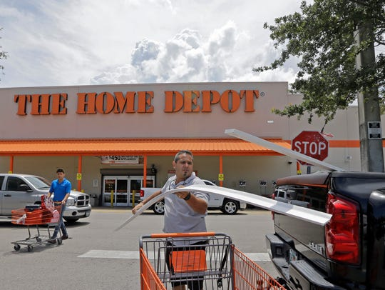 Vicente Aguiar loads garage door trims into his pickup outside a Home Depot in Hialeah, Fla.
