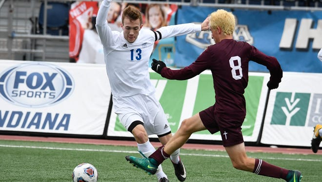 Memorial's Andrew Cross attempts to dribble around a Concordia Lutheran defender in the state championship game. Cross was named the Gatorade Player of the Year in the state of Indiana for the second year in a row.