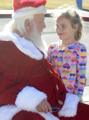 Yerington Elementary School first-grader Serenity Lorentz visits with Santa.