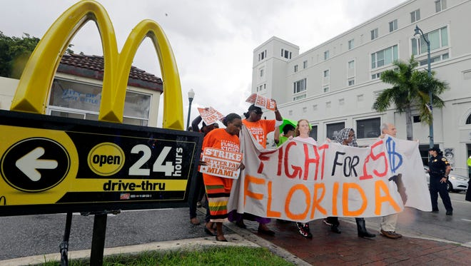 People protest for higher wages outside a McDonald's restaurant in the Little Havana area of Miami in December. McDonald's workers in 19 cities have filed complaints over burns from hot grills and fryers and other workplace hazards, according to labor organizers. The complaints are the latest move in an ongoing campaign to win pay of $15 an hour and unionization for fast-food workers, in part by publicly pressuring McDonald's to come to the bargaining table.