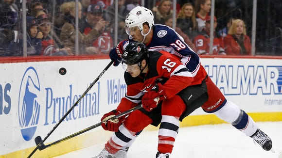 New Jersey Devils defenseman Steven Santini (16) battles for the puck with Columbus Blue Jackets center Boone Jenner (38) during the first period of an NHL hockey game, Friday, Dec. 8, 2017, in Newark, N.J.