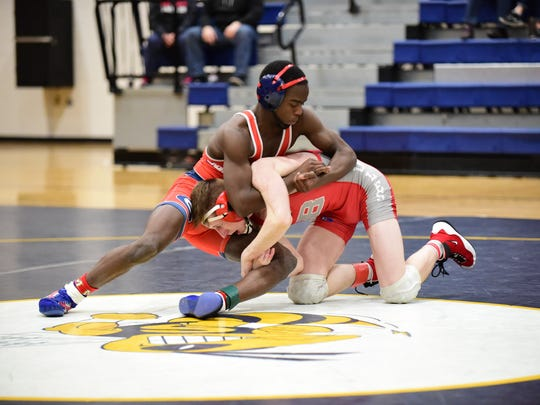 In the 119-pound bout to open Wednesday's D1 team regional final at Saline, Westland John Glenn's Caleb Meekins (left) gets an edge against Temperance Bedford's Cade Sutter.
