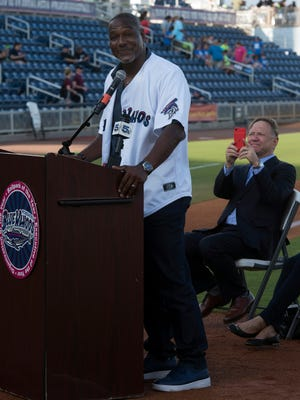 NFL Hall of Famer, Derrick Brooks, left, speaks to Blue Wahoos fans after announcing he would be joining the Wahoos ownership group, Wednesday, May 23, 2018, while team owner Quint Studer, takes a behind the scenes photo.  Brooks joins Bubba Watson as minority owners of Studer's minor league baseball team.