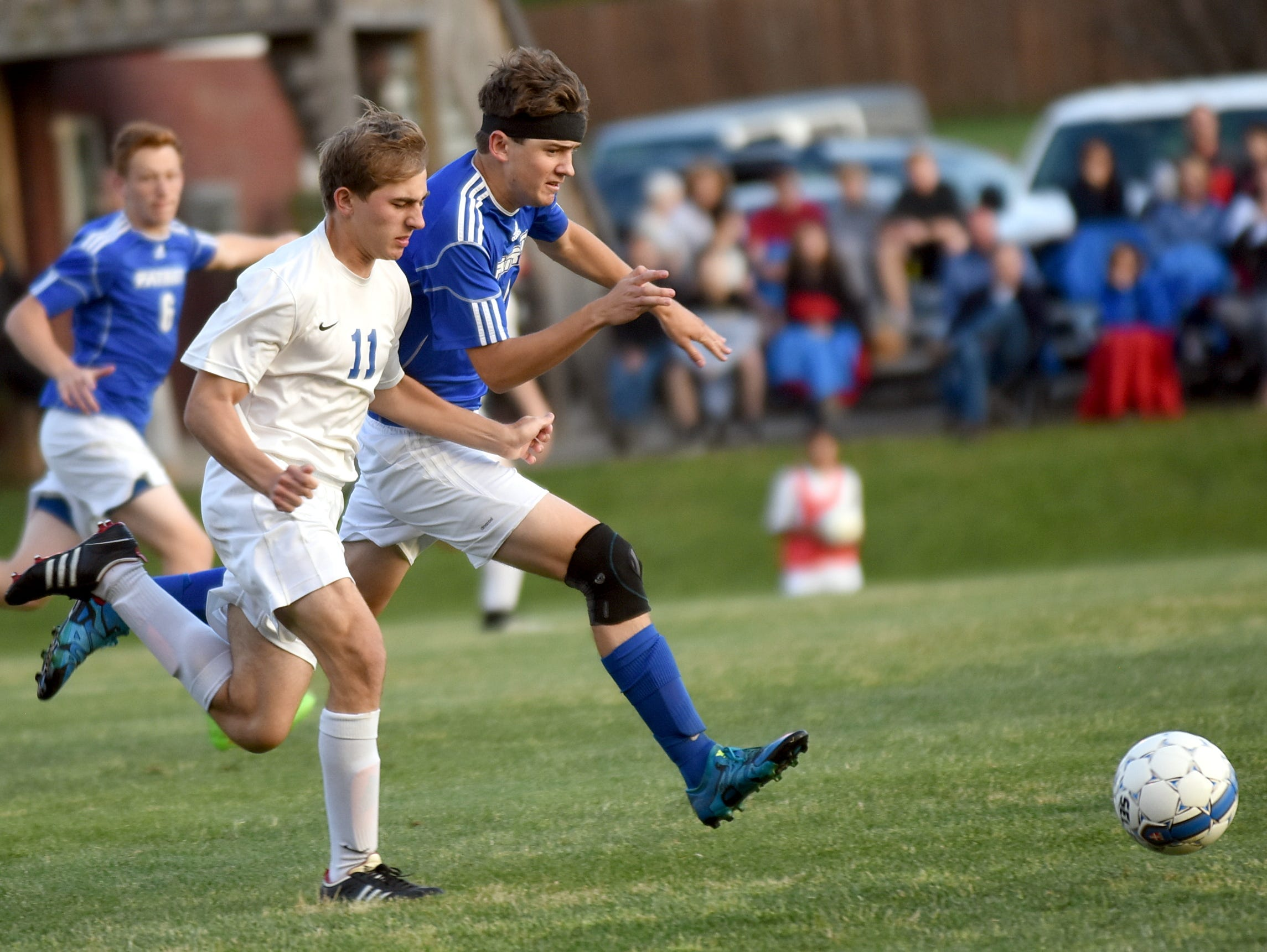 White House High senior Mark Lees runs on to a through-ball as Page senior Ethan Hester battles for possession during first-half action.