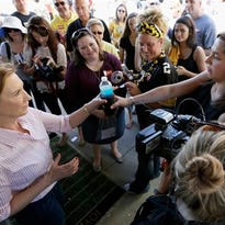 "In this photo taken Sept. 26, 2015, Republican presidential candidate Carly Fiorina receives a bottle of water from her assistant Rebecca Schieber, right, as they visit with tailgaters before a University of Iowa football game in Iowa City, Iowa. Schieber has landed in a rare position on the presidential campaign trail, working as a ""body woman."" The job isn't to provide to security, as the name implies, but rather to act as more of a personal assistant, adviser and sidekick."