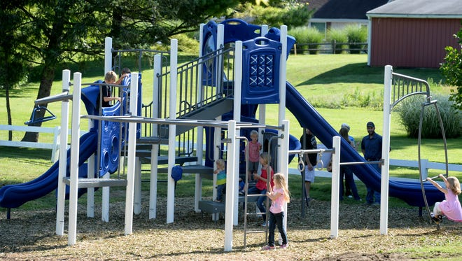 Kids try out new playground equipment Saturday, Aug. 22, 2015 at Maplewood Park in Centerville.