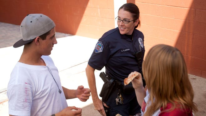 Mesa Police Officer Karrie Flanigan talks to students Richard Lodge and Jolie Smithson at Red Mountain High School in 2012.