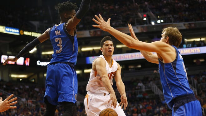 Phoenix Suns guard Devin Booker (1) passes the ball between Dallas Mavericks forwards Nerlens Noel (3) and Dirk Nowitzki (41) during the first quarter at Talking Stick Resort Arena in Phoenix, Ariz. April 9, 2017.