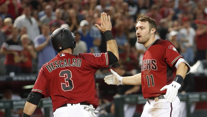 Arizona Diamondbacks' Daniel Descalso (3) high fives A.J. Pollock (11) after they both scored against the Houston Astros during the sixth inning at Chase Field in Phoenix, Ariz. May 6, 2018.