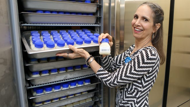 Julie Bouchet-Horwitz, founder and executive director of the New York Milk Bank, stands before a refrigerator full of breast milk at the Hastings milk bank.