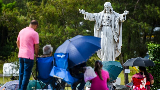 Family and friends gather at the gravesites of loved ones as an All Souls Day Mass is celebrated at the Our Lady Of Peace Memorial Gardens in Yona on Thursday, Nov. 2, 2017.