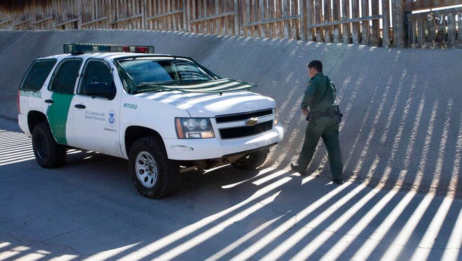 A Border Patrol agent walks along a border fence on an access road in Nogales, Ariz., in January.