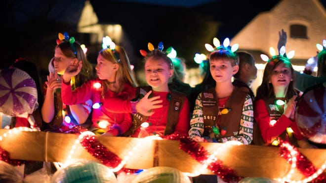 Girl Scouts wave to the crowd Saturday during the 2018 Pfestival of Lights in downtown Pflugerville.