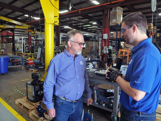Lane Brock, left, president of WPT Power , talks with Jeremy Bodine, an application engineer, in the manufacturing area of the business. The company employs 37 people and was recently named as a top 100 company to work for in Texas.
