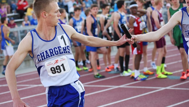 Sioux Falls Christian's Lance VanZee (right) hands the baton off to Caleb DeWeerd during the high school boys class A 4 x 800 meter relay on Friday for the 2017 Howard Wood Dakota Relays.