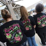 Wendy Palmer, left, of Ocean Springs, her cousin, Amanda Dean, of Eupora, and Amanda's mother, Evelyn Strickland, of Kilmichael, don matching Black Friday t-shirts while shopping at the Outlets of Mississippi in Pearl on Friday. The trio got started at 4 p.m. on Thursday, shopped until the wee hours and were back at it early Friday morning.