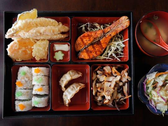 The Dinner Bento Box features Teriyaki Salmon, Tempura Shrimp, a California Roll and Squid Salad among other Japanese treats.