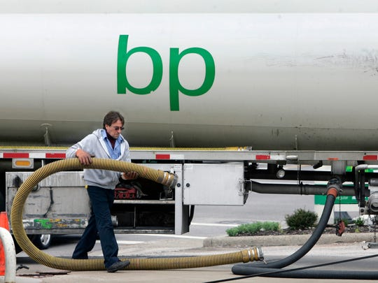A worker prepares to fill the big underground storage tanks with gasoline from his tanker truck at a BP service station.