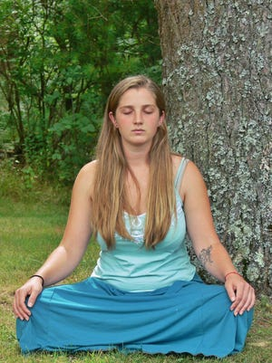 A woman is in a sitting meditation on the grounds of the Insight Meditation Society (IMS) Retreat Center in Barre, Mass.