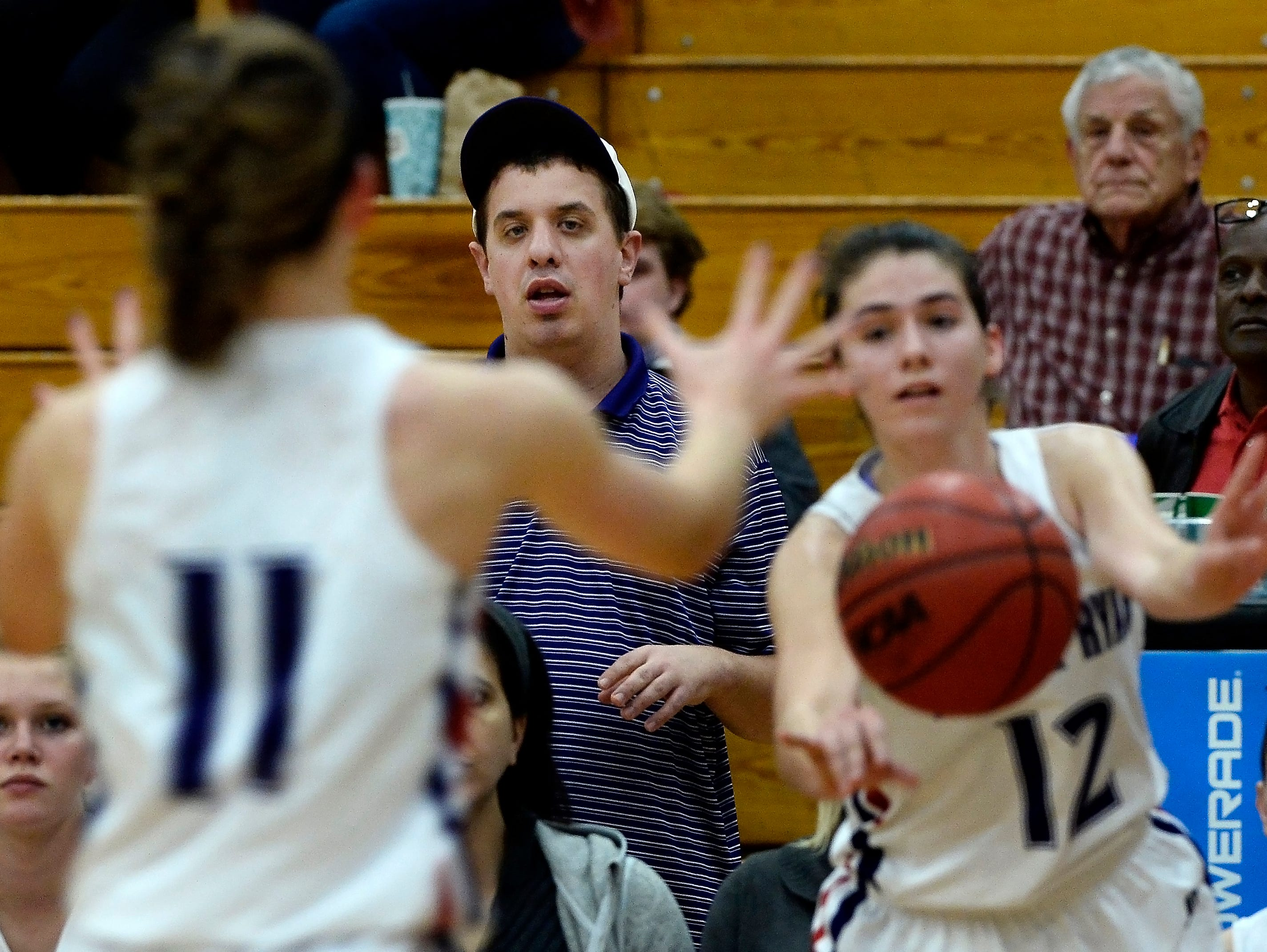 Sean Druffel watches Father Ryan High School girls varsity basketball players Audrey Burdge (11) and Olivia Rolick (12) play during a game on Tuesday, Jan 5, 2016, in Nashville, Tenn.
