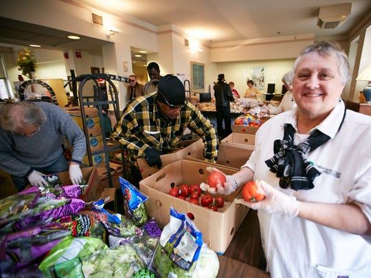 Linda Brennan-Jones helps with distribution of fresh vegetables and fruit.