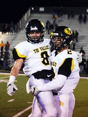 Tri-Valley linebacker Nathan Lawler picks up teammate Caleb Craig after the Scotties' 24-6 win against Akron St. Vincent-St. Mary in a Division III state semifinal game on Friday night at Massillon Perry. The win sent the Scotties to their first state championship game in school history.