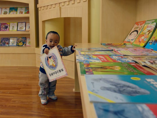 A young patient at a Sanford World Clinic in Kunming, China, examines his reading options.
