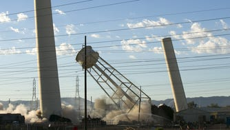 The two stacks and water tower of the nearly 80-year old oil-fired steamed Phoenix Power Plant are demolished by implosion in Phoenix on October 1, 2016.
