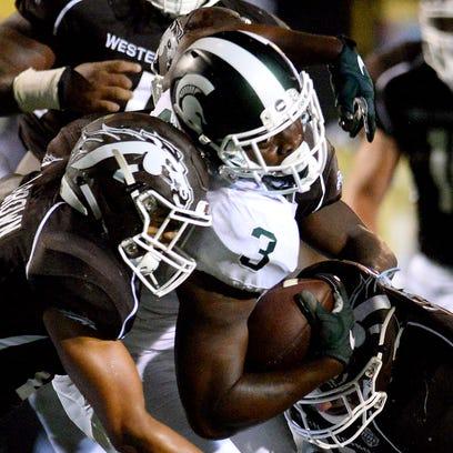 Spartans running back LJ Scott tries to battle through