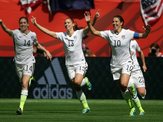 From left, United States' Morgan Brian, Alex Morgan, and Carli Lloyd celebrate after Lloyd scored her second goal of the match against Japan during the first half of the FIFA Women's World Cup soccer championship in Vancouver, British Columbia, Canada, Sunday, July 5, 2015.