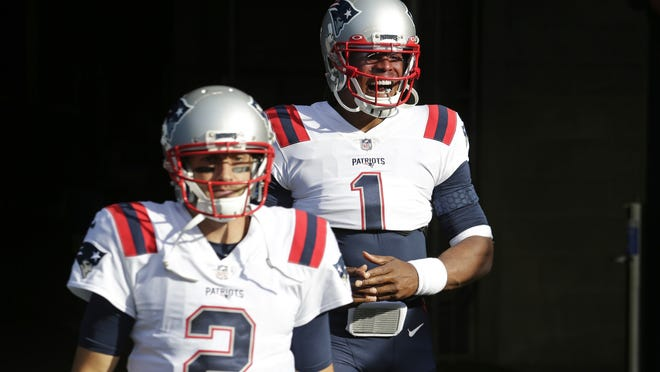 New England quarterback Cam Newton, right, and backup quarterback Brian Hoyer, left, walk out of the tunnel before a game earlier this season. Reports say Hoyer will step in under center on Monday night after Newton was diagnosed with the coronavirus.