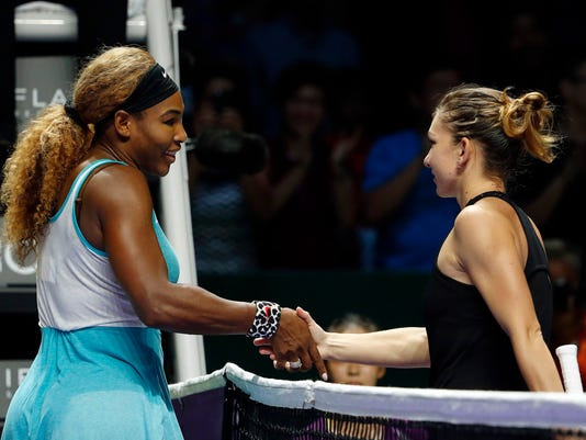 Williams of the U.S. shakes hands with Halep of Romania after winning the women's singles final tennis match of the WTA Finals at the Singapore Indoor Stadium