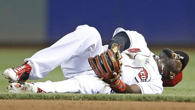 Reds second baseman Brandon Phillips grimaces in pain after injuring his left thumb while diving for a ground ball Wednesday.