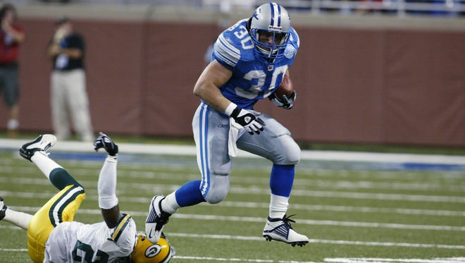 DETROIT - SEPTEMBER 22:  Fullback Cory Schlesinger #30 of the Detroit Lions runs the ball as cornerback Tod McBride #27 of the Green Bay Packers goes down during the game on September 22, 2002 at Ford Field in downtown Detroit, Michigan. The Packers defeated the Lions 37-31. (Photo by Tom Pidgeon/Getty Images)