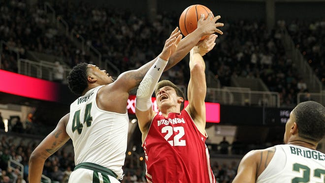 Wisconsin forward Ethan Happ has his shot blocked by Michigan State forward Nick Ward during the first half on Friday night in East Lansing, Mich.