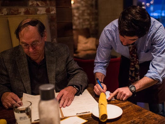 Noah Wimberly, right, writes down a drink order from