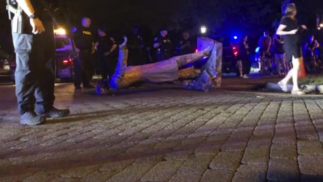 In this image from video, police stand near a toppled statue of Jefferson Davis on Wednesday night, June 10, 2020, in Richmond, Va. Protesters tore down the statue of Confederate President Davis along Monument Avenue. The statue in the former capital of the Confederacy was toppled shortly before 11 p.m., news outlets reported.