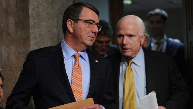 Ashton Carter talks with Senate Armed Services Committee Chairman John McCain, R-Ariz., as they arrive for Carter's confirmation hearing.